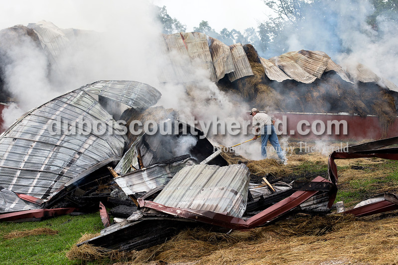 Gerry Verkamp of Schnellville raked hay away from a barn that was destroyed by fire this morning near the Steven and Starla Rothgerber home at 5701 S. 600E near Kyana. The St. Anthony Volunteer Fire Department responded to a call at 6:30 a.m. of a fully involved barn fire. The department was assisted by units from Schnellville and Ferdinand.<br /> Dave Weatherwax/The Herald