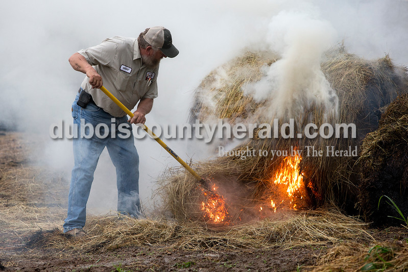Gerry Verkamp of Schnellville broke apart a large hay bale that was on fire so firefighters could extinguish it this morning near Kyana. Dave Weatherwax/The Herald