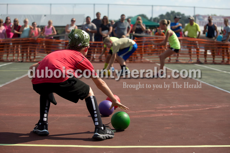 Erica Lafser/The Herald<br /> Aiden Nord of St. Anthony, 8, reached for a dodgeball as he kept an eye on the opposing team during the dodgeball tournament at St. Anthony Firemen's Fest on the tennis courts at St. Anthony Community Center in St. Anthony.