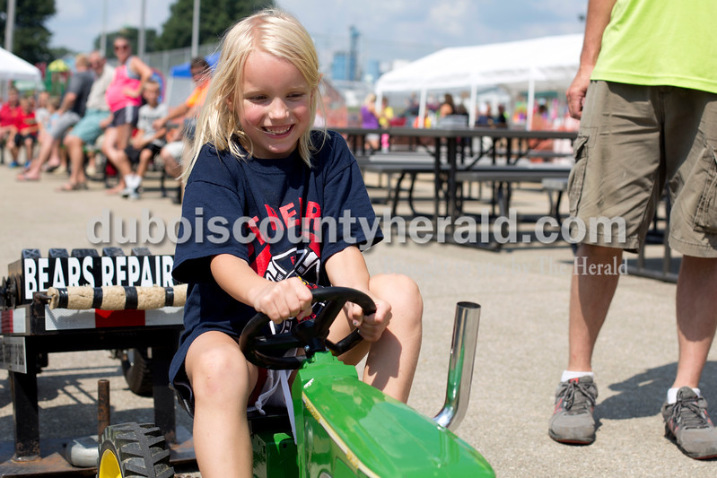 Erica Lafser/The Herald<br /> Kynsley Gogel of St. Henry, 5, smiled under the pressure of the kiddie tractor pull during the St. Anthony Firemen's Fest on Saturday at St. Anthony Community Center in St. Anthony.