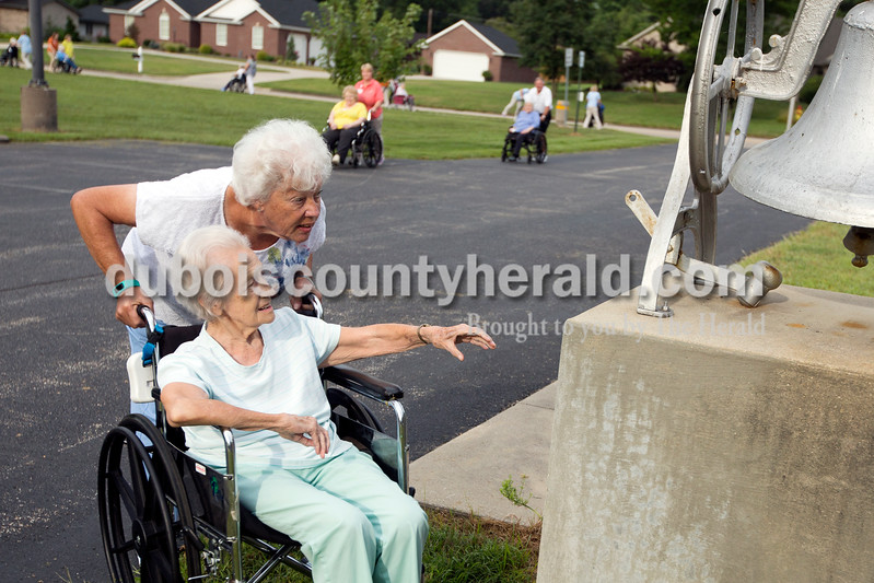 Ariana van den Akker/The Herald<br /> St. Charles resident Ruby Thimling reached to ring a bell as volunteer Sylvia Priser of Jasper encouraged her at the First Presbyterian Church in Jasper during the Friday fitness walk at St. Charles Health Campus in Jasper. Every Friday this summer, employees or volunteers have taken residents on a walk along the St. Charles Street walking path to the church and back.