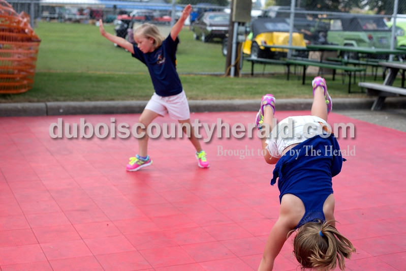 """Erica Lafser/The Herald<br /> Abby Sermersheim of Huntingburg, 8, left, and Leigha Nord of St. Anthony, 6, did cartwheels in front of the stage set up at St. Anthony Community Center during the St. Anthony Firemen's Fest on Saturday in St. Anthony. """"I used to be in gymnastics but I quit it for softball,"""" Nord said."""