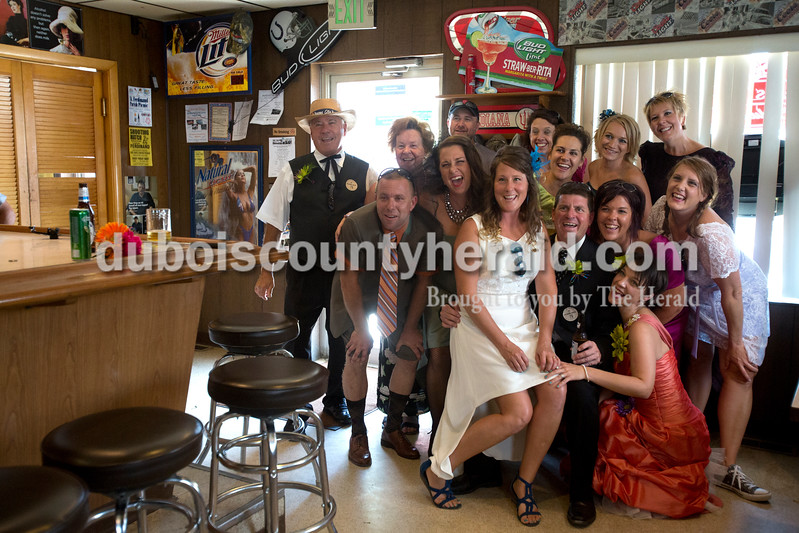 Erica Lafser/The Herald<br /> Friends and family of Natalie and Jeremy Combs of Mentor posed for the bartender to take a picture during the celebration of the Combs' 15th wedding anniversary on Saturday at Arnie's Tavern in St. Anthony. Everyone came dressed in the worst dresses they could find thrift shopping.