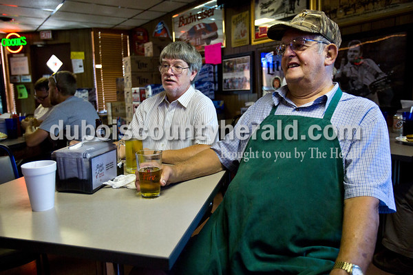 After grilling up ribs, steak burgers and chicken, Richard Helming, right, chatted with Bob Bumm of Fulda, and a few other customers in Fleig's restaurant on Thursday in Ferdiand. Helming owned the restaurant for over 30 years, and although he sold it 10 years ago, he still helps out a few days a week and grills every thursday morning during the warm months.  Alisha Jucevic/The Herald