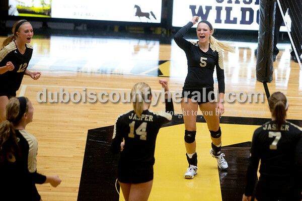 Jasper's Kinsey Bromm, left, Teyah Leinenbach and Michala Flamion celebrated a point during Tuesday night's game against Heritage Hills in Jasper. The Wildcats won in three sets. Ariana van den Akker/The Herald