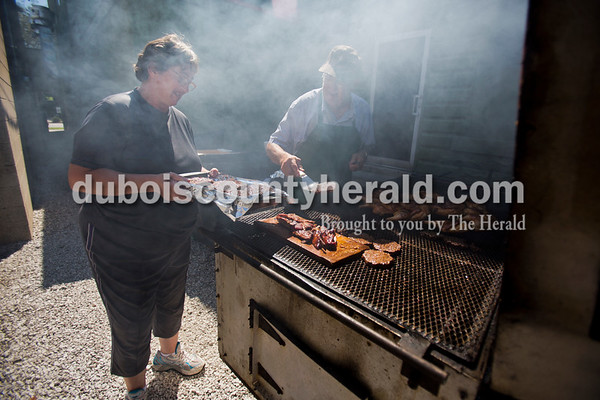 """Fleig's cook Karen Ketzner held a pan as Richard Helming, 75, loaded it up with freshly grilled steak burgers outside Fleig's restaurant on Thursday in Ferdinand. Helming owned Fleig's for over 30 years, and although he sold it 10 years ago, he still helps out a few days a week and grills every thursday during the warm months. """"People enjoy coming in to talk to him,"""" Ketzner said. """"He's a guy that everybody likes.""""   Alisha Jucevic/The Herald"""