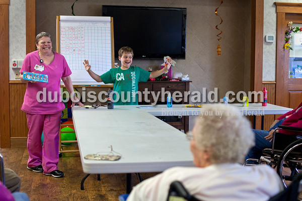 """Activities assistant Jan Egg, left, and Dakota played """"Minute To Win It"""" with Northwood residents April 4. """"It's like he's never met a stranger,"""" said Jennifer Wilson, the marketing and resource development director at Northwood. """"He's not reserved at all."""""""