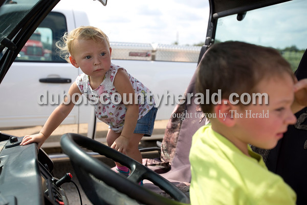 Erica Lafser/The Herald Emery Mehringer of Ireland, 2, left, played with her brother Bryant, 3, in their neighbor's Gator that their dad, Eric, borrowed for the Celestine Volunteer Fire Department's annual tractor pull on Sunday at the Celestine Community Club in Celestine so they would not have to walk back and forth all day long.