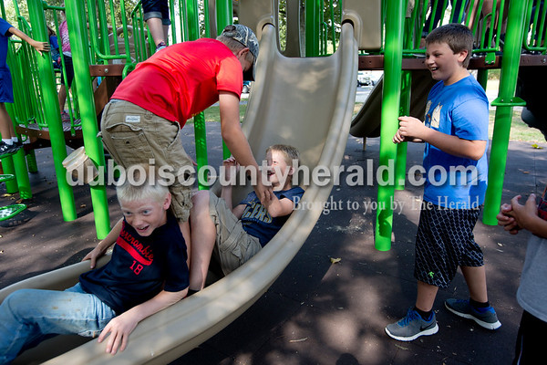 Ariana van den Akker/The Herald On Wednesday evening, members of the St. Celestine and St. Raphael junior high and high school youth groups flocked to the Dubois Community Park in Dubois for a cookout to start the new school year. Gavin Knies, 10, left, Nicholas Leuken, 12, and Carter Beckman, all of Dubois, 13, played on the slide as their friend Landon Gutgsell of Celestine, 11, right, watched during the event.