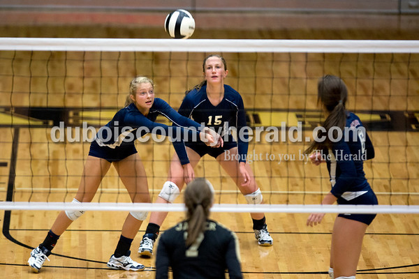 Heritage Hills' Abby Wetzel, left bumped the ball as teammates Abby Wahl, center, and Claire Dilger supported her during Tuesday night's game against Jasper in Jasper. The Wildcats won in three sets. Ariana van den Akker/The Herald