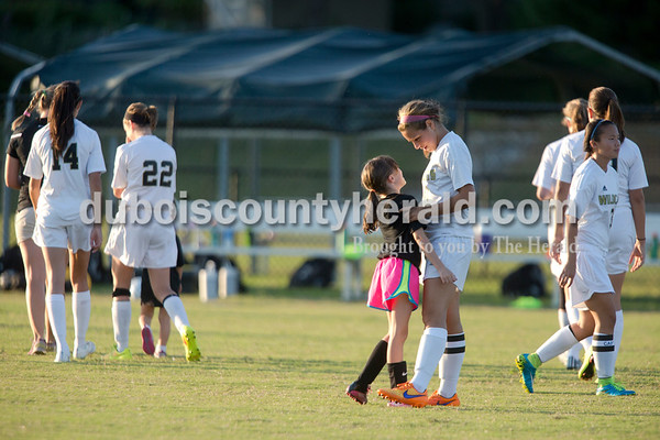 """Erica Lafser/The Herald Ava Claire Werne of Jasper, 8, gave Jasper's Brittany Haskins a hug during their warm up for Wednesday night's game against Evansville Harrison in Jasper. Werne was one of the young girls to win the """"Jasper Soccer Experience,"""" in which the young girls were able to warm up, be announced and sit with the Jasper girls soccer team during this game. The team knew the girls well from previous soccer camps. The Wildcats won 8-1."""