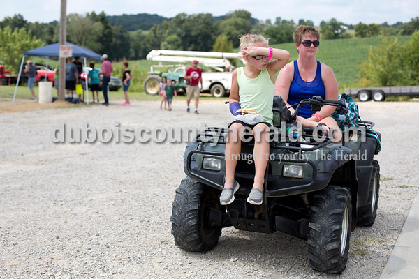 """Erica Lafser/The Herald Tatum Wehr of Ireland, 7, left, watched the kiddie tractor pull at the Celestine Volunteer Fire Department's annual tractor pull on Sunday at the Celestine Community Club in Celestine from a distance with her mom, Kris. Tatum was also waiting for her turn to participate, hoping to place first. """"If I get first place and my dad doesn't, I told him that means I beat him,"""" Tatum said about her dad, Jason, who participated in the bigger tractor pull."""