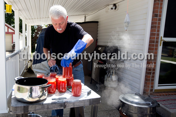 """Ariana van den Akker/The Herald Taking advantage of the nice weather on Tuesday, Daniel Lawson of Jasper canned homemade tomato juice in his driveway. Lawson said it's been a """"terrible year"""" for his garden but he still had enough tomatoes to make a batch of juice."""