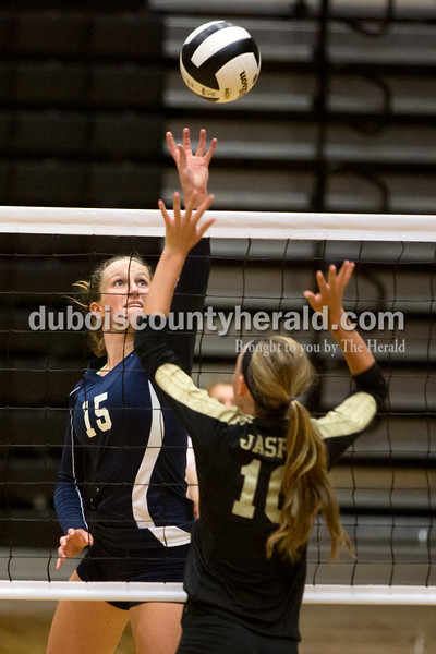 Heritage Hills' Abby Wahl sent the ball over the net as Jasper's Avery Bell blocked during Tuesday night's game in Jasper. The Wildcats won in three sets. Ariana van den Akker/The Herald