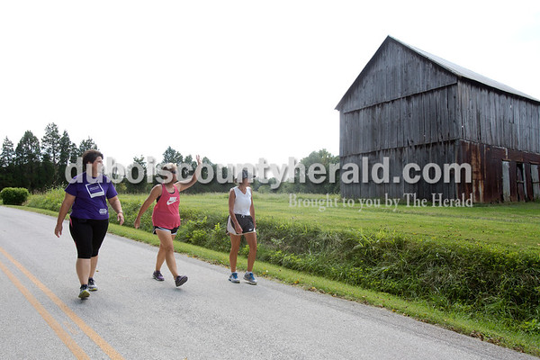 """Erica Lafser/The Herald Jean Lancaster of Washington, left, walked with her cousins Theresa Jahn and Heather Tretter, both of Huntingburg, and sisters, on their normal 6 mile route on Tuesday afternoon in Huntingburg along county roads like this one, 630 S. Jahn waved to her neighbor, Mary Meyer of Huntingburg. They walk for exercise, but also participate in events such as the Alzheimer's walk that they have done together the past two years. Earlier on this Tuesday, the three attended the funeral of their uncle who passed due to Alzheimer's. """"[Alzheimer's has] effected us all in many ways,"""" Lancaster said."""