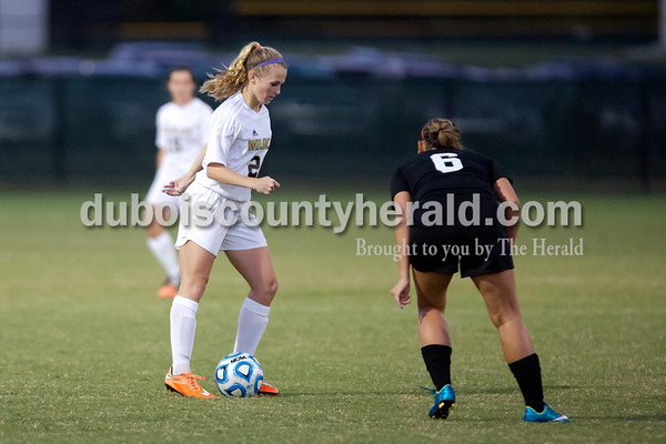 Erica Lafser/The Herald Jasper's Madisyn Hunt fought to keep possession of the ball from Danielle Schall during Wednesday night's game against Evansville Harrison in Jasper. The Wildcats won 8-1.
