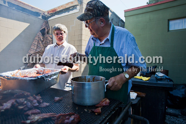 """Lifelong Ferdinand resident Richard Helming, 75, dipped freshly grilled ribs into barbecue sauce and placed them in a pan outside Fleig's restaurant on Thursday in Ferdinand. Restaurant customer Bob Bumm of Fulda held the pan for Helming. Helming owned Fleig's for over 30 years, and although he sold it 10 years ago, he still helps out and grills every thursday morning during the spring and summer. Customers often come outside to chat with Helming as he grills. """"It's hard to walk away from it when you've been there for 35 years,"""" Helming said. """"Still got a lot of my friends who still come back for a meal.""""  Alisha Jucevic/The Herald"""