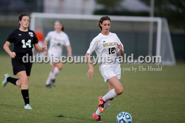 Erica Lafser/The Herald Jasper's Annie Stout chased her opponent Elizabeth Roberts to the ball during Wednesday night's game against Evansville Harrison in Jasper. The Wildcats won 8-1.
