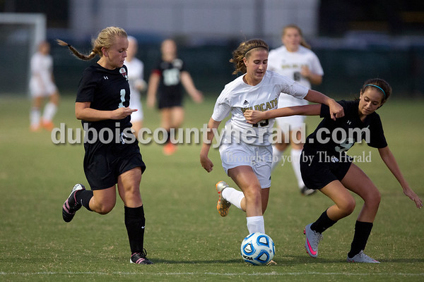 Erica Lafser/The Herald Jasper's Erin Leinenbach fought for possession against Maddie Jesop, left, and Maddie Moore during Wednesday night's game against Evansville Harrison in Jasper. The Wildcats won 8-1.