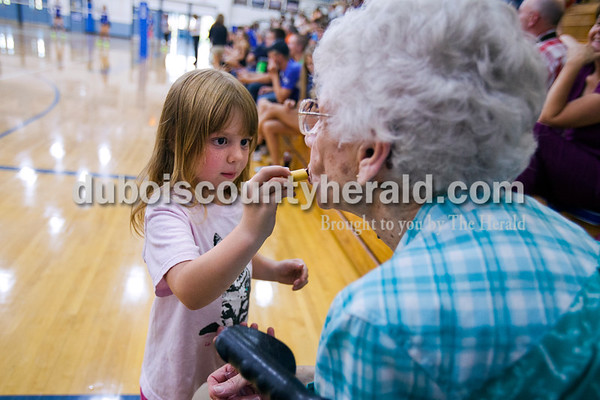"""Dexi Kirchoff of Celestine, 5, applied lipstick on her grandmother, Lois Kirchoff of Bloomfield, during Thursday's volleyball match between Northeast Dubois and North Knox  at the Northeast Dubois gym. """"Everytime she (Lois Kirchoff) comes she has to bring her makeup,"""" said Dexi's father, Brian Kirchoff. He said it's the grandmother and granddaughter's routine at every game. Dexi's older sister and Lois' granddaughter, Addison Kirchoff, plays on the Jeeps.  Alisha Jucevic/The Herald"""