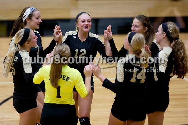 Jasper's Michala Flamion, left, Reagan Hochmeister, Kinsey Bromm, Jocelynn Morrow, Maria Gobert  and their teammates got pumped up before the third set of Tuesday night's game against Heritage Hills in Jasper. The Wildcats won in three sets. Ariana van den Akker/The Herald