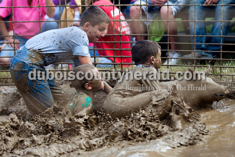 Alisha Jucevic/The Herald<br /> <br /> Caleb Hochgesang of Santa Claus, 10, Kayden Bell of Mariah Hill, 10, and Sheldon Smith of Fulda, 11, dove at the pig during the Dale Fall Festival's annual hog wrestling contest Saturday.