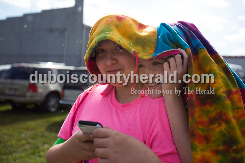 Alisha Jucevic/The Herald<br /> <br /> Abby VanHoosier, 14, and Emily Reiner, 14, both of Dale, hid under Abby's sweatshirt as it started to rain before the Dale Fall Festival's annual hog wrestling contest Saturday.