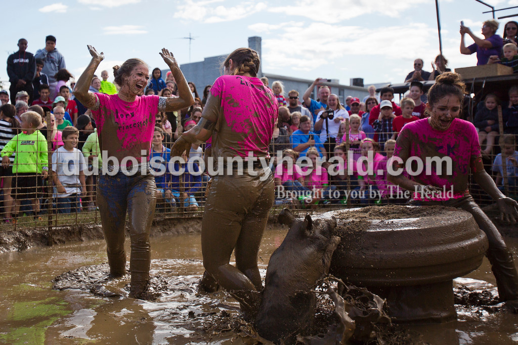 Alisha Jucevic/The Herald<br /> <br /> 2015 Miss Dale Fall Festival Hope Davis of Dale, 17, left high-fived her teammate Faith Hall of Santa Claus, 16, after the hog wrestling contest Saturday at the Dale Fall Festival.