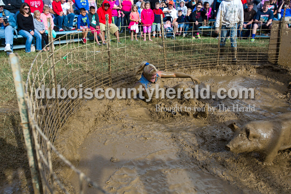 Alisha Jucevic/The Herald<br /> <br /> Penni Beckman-Williams of Tennyson fell backward after wrestling the pig onto a tire in the center of the pit during the Dale Fall Festival's annual hog wrestling contest Saturday. This is Penni's 29th year of hog wrestling.