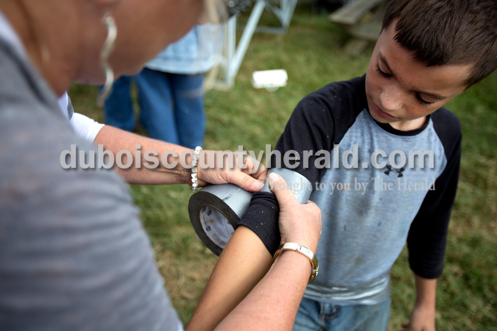 Alisha Jucevic/The Herald<br /> <br /> DeeDee Begle of Fulda helped Shelden Smith of Fulda, 11, tape up his shirt sleeves before the Dale Fall Festival's annual hog wrestling contest Saturday. The duct tape is used in an attempt to stop mud and chunks of dirt from getting under your shirt.