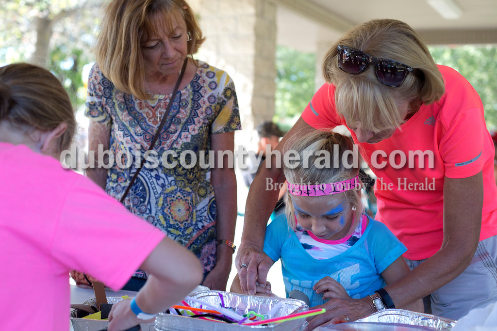 Erica Lafser/The Herald<br /> Connie Lueken helped her granddaughter, Kinley Hawkins, 5, make a finger puppet while her sister, Donna Trafton, all of Ferdinand, watched the activity during the Ferdinand Folk Festival on Saturday at 18th Street Park in Ferdinand.