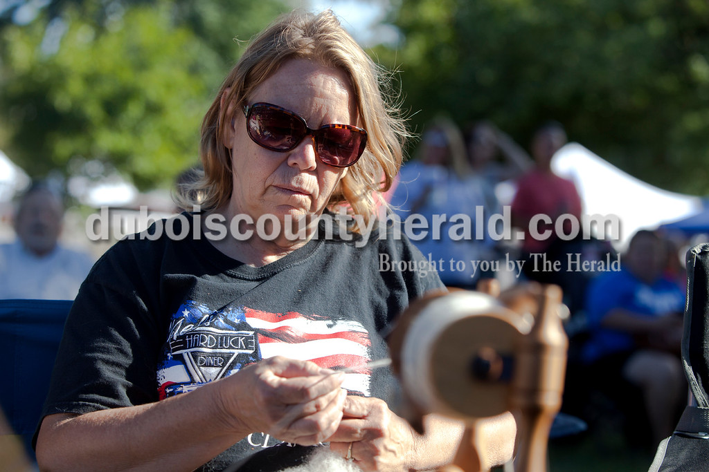 Erica Lafser/The Herald<br /> Rebecca Hedinger of Ferdinand spun yarn from the fur of her herd of alpacas during the Ferdinand Folk Festival on Saturday at 18th Street Park in Ferdinand.