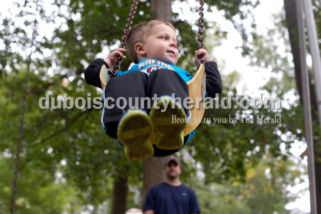 Erica Lafser/The Herald<br /> Jason Calhoun of Huntingburg pushed his 2-year-old son, Owen, on the swings during the Holland Community Fest on Saturday at Holland Park in Holland.
