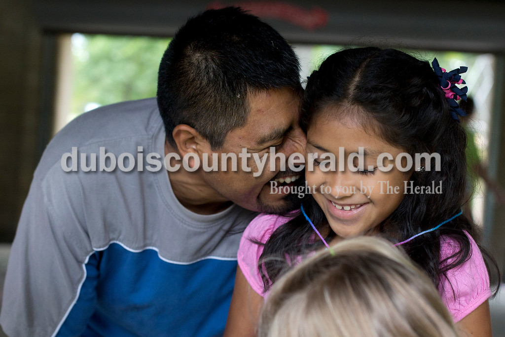 Erica Lafser/The Herald<br /> Ricardo Venegas Barahora of Holland, left, laughed with his daughter Victoria, 7, during the Holland Community Fest on Saturday at Holland Park in Holland.