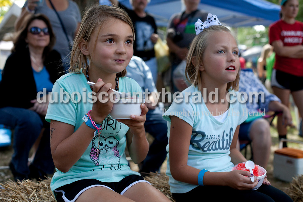 """Erica Lafser/The Herald<br /> Molly Scherzer of Lamar, 9, left, enjoyed some music performed by Hayley Payne and a snow cone with her cousin Brooklyn Lewis of Bloomington, 9, during the Ferdinand Folk Festival on Saturday at 18th Street Park in Ferdinand. """"We got her autograph and talked to her... she's really nice and her voice is good,"""" Lewis said."""