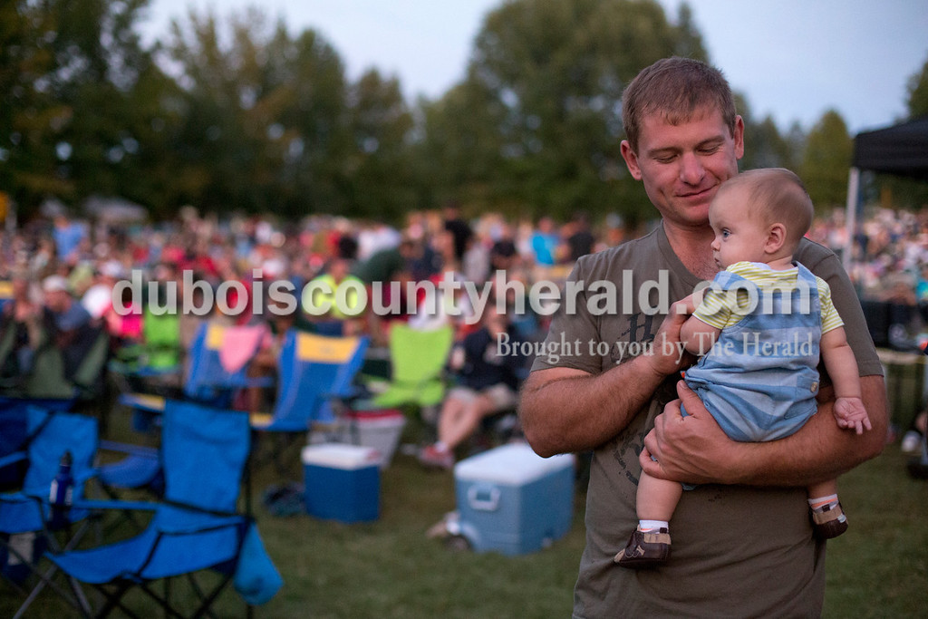 Erica Lafser/The Herald<br /> Aaron Rasche of Jasper held his 7-month-old son, Bennett, during the Ferdinand Folk Festival on Saturday at 18th Street Park in Ferdinand.