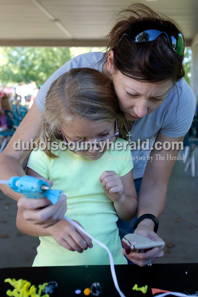 Erica Lafser/The Herald<br /> Ireland native Heather Furniss of Evansville helped her daughter Sophie, 6, make a puppet during an activity by Squallis Puppeteers from Louisville at the Ferdinand Folk Festival on Saturday at 18th Street Park in Ferdinand.