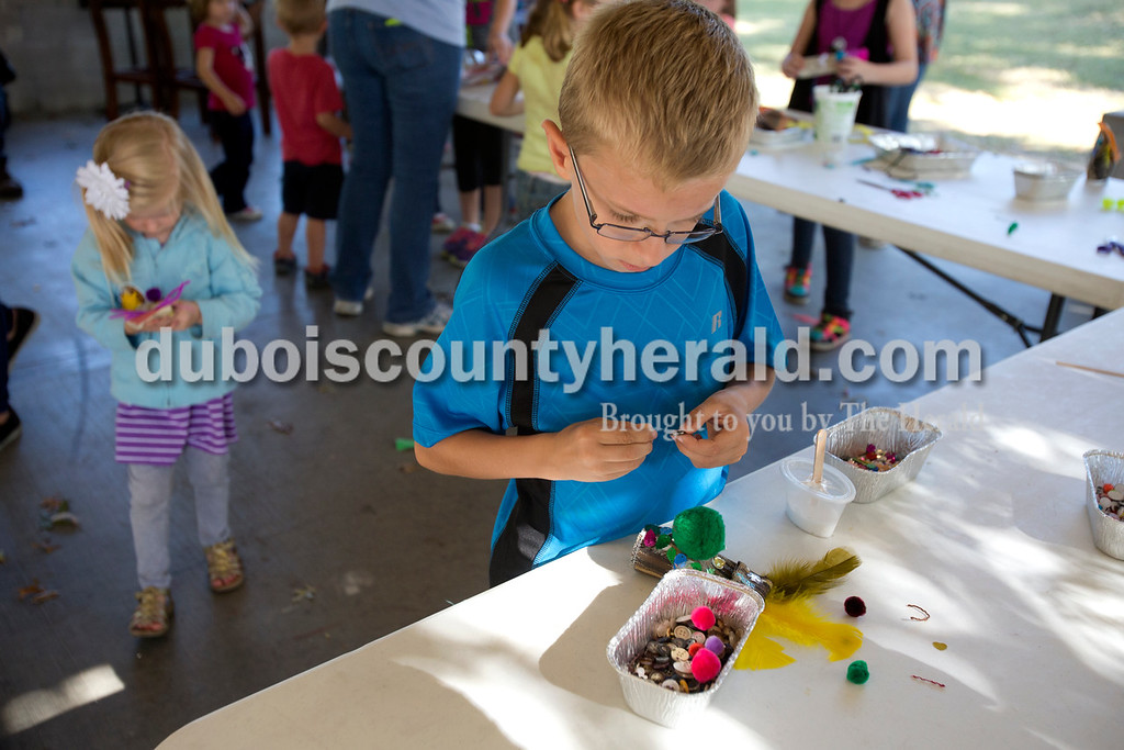 Erica Lafser/The Herald<br /> Chase Niehaus of St. Anthony, 8, made a finger puppet during an activity put on by Squallis Puppeteers from Louisville during the Ferdinand Folk Festival on Saturday at 18th Street Park in Ferdinand.