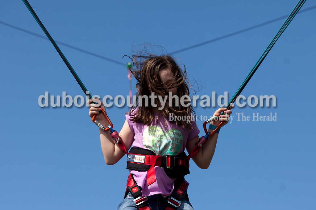 Erica Lafser/The Herald<br /> Addison Chapman of Jasper, 9, flew high in the air off a trampoline during the Ferdinand Folk Festival on Saturday at 18th Street Park in Ferdinand.