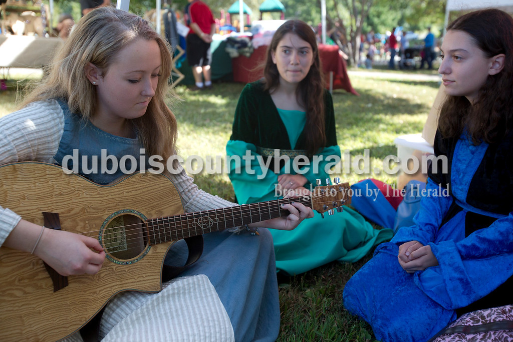 Erica Lafser/The Herald<br /> Anna Buechler of Jasper, 18, left, played the guitar and sang with Jenna Steltenpohl of Ireland, 18, and her sister Emma Steltenpohl, 16, behind a booth at Ferdinand Folk Festival on Saturday at 18th Street Park in Ferdinand.