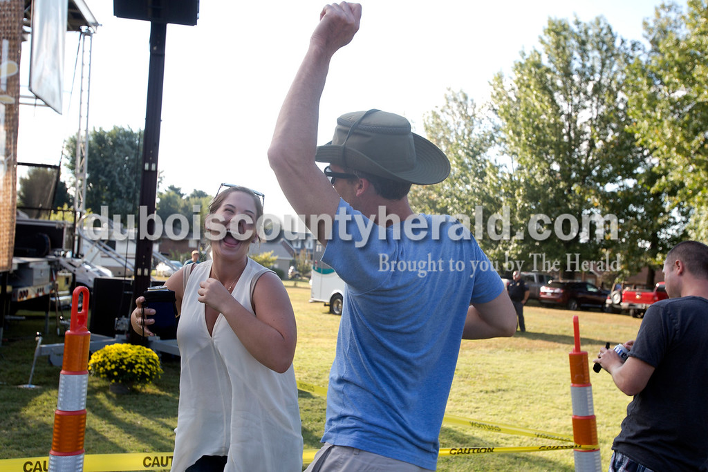 Erica Lafser/The Herald<br /> Jessica Sanders of Jasper, left, laughed at Andy Gubbins of Jasper's dancing during the Ferdinand Folk Festival on Saturday at 18th Street Park in Ferdinand.