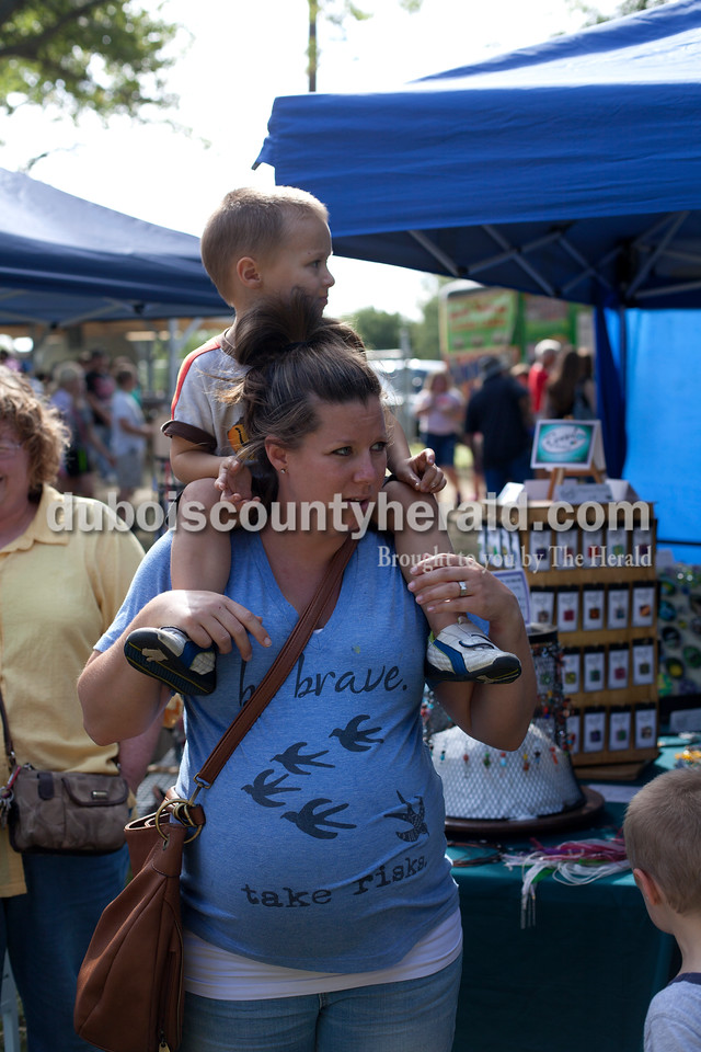 Erica Lafser/The Herald<br /> Rachel Steckler of Huntingburg, held one of her kids, Cooper, 2, on her shoulders during the Ferdinand Folk Festival on Saturday at 18th Street Park in Ferdinand.