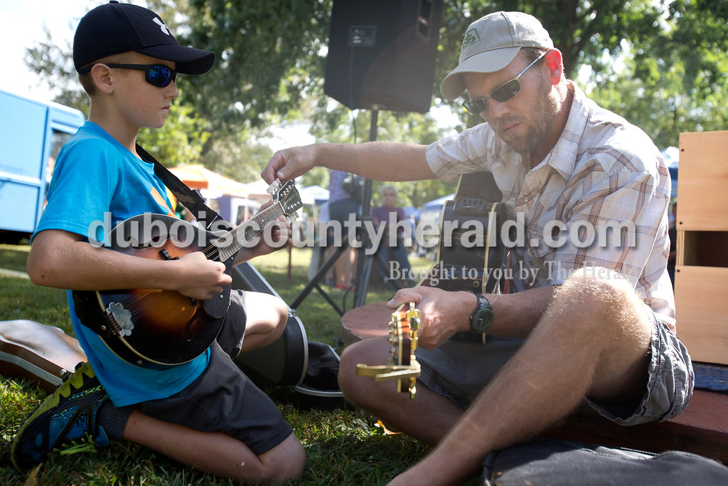 """Erica Lafser/The Herald<br /> Ferdinand native Andy Hagedorn of Bristow, right, tuned his son's, Henry, 11, mandolin before their performance at the Market Stage during Ferdinand Folk Festival on Saturday at 18th Street Park in Ferdinand. """"(We play) mostly for fun,"""" Andy said."""