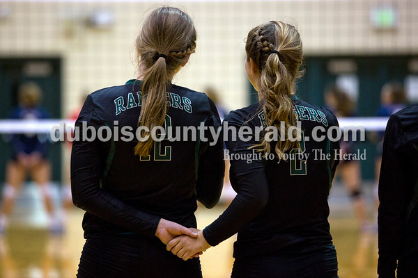 Forest Park's Taylor Bayer and Kendra Schipp held hands during the National Anthem before Monday night's game at Forest Park High School in Ferdinand. Heritage Hills won in three sets.  Alisha Jucevic/The Herald