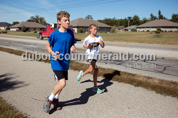 Ariana van den Akker/The Herald Jasper Middle School seventh-grader Kyle Allen, left, and sixth-grader Kiersten Wagner ran together at cross country practice after school on Tuesday. Kyle and Kiersten both have cerebral palsy and have formed a sort of running partnership for practices.