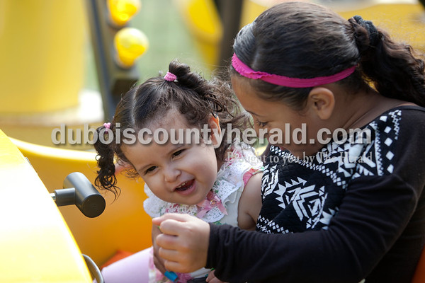 Erica Lafser/The Herald Kimberly Cortez of Jasper, 6, right, rode the banana airplane ride with her 1-year-old sister, Yahaira, during the Herbstfest on Saturday at Huntingburg City Park in Huntingburg.