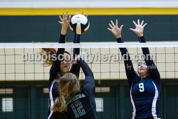 Forest Park's Taylor Bayer spiked the ball as Heritage Hills' Jessica Bertke, left, and Sydney Scherry jumped up to block during Monday night's game at Forest Park High School in Ferdinand. Heritage Hills won in three sets.  Alisha Jucevic/The Herald