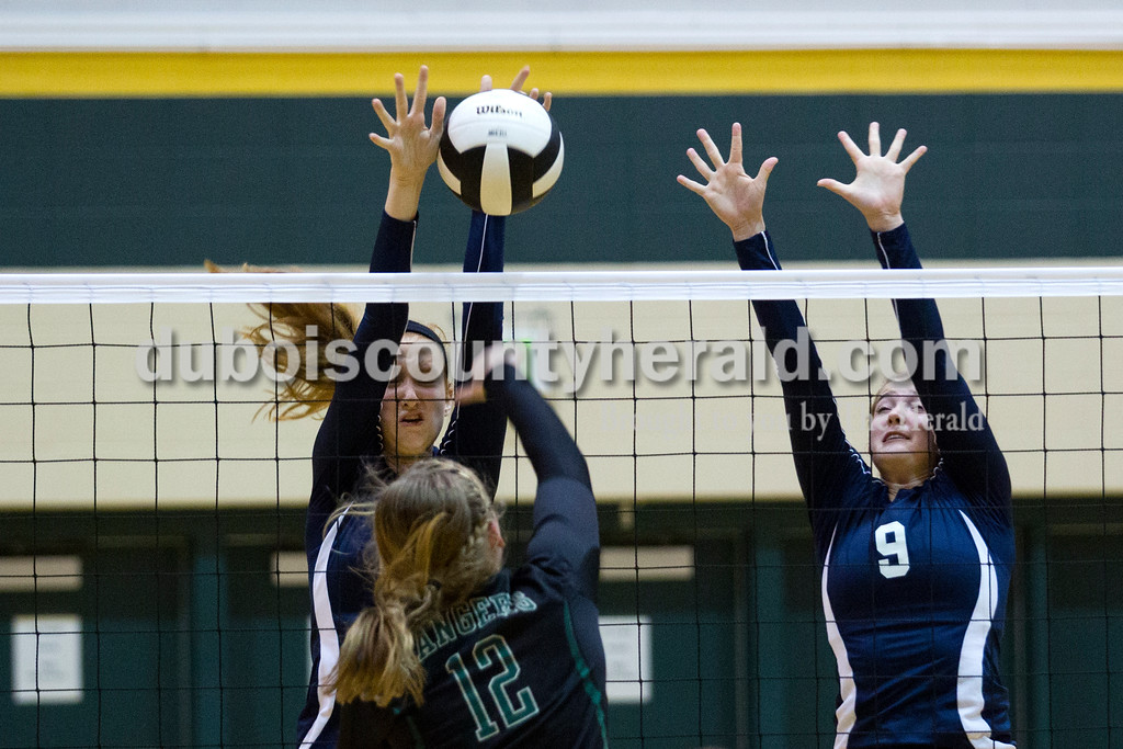Forest Park's Taylor Bayer spiked the ball as Heritage Hills' Jessica Bertke, left, and Sydney Scherry jumped up to block during Monday night's game at Forest Park High School in Ferdinand. Heritage Hills won in three sets. <br /> Alisha Jucevic/The Herald