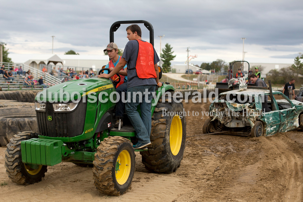 Erica Lafser/The Herald<br /> Wyatt Goeppner of Jasper, 16, drove the tractor with an additional pair of eyes helping from Kaleb Stenftenagel of Jasper, 16, as they pulled Greg Gerber of Winslow after the mini-stock demolition derby on Saturday at the Dubois County 4-H Fairgrounds.