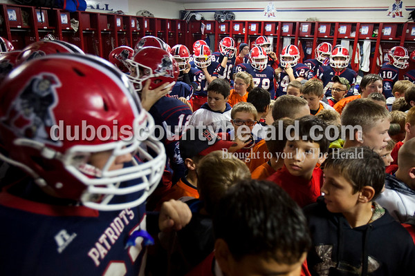 Members of the Minutemen Tackle and Flag Football program gathered in the middle of the locker room to see Heritage Hills' pre-game routine before Friday night's game in Lincoln City. Heritage Hills defeated Southridge 17-7.   Alisha Jucevic/The Herald